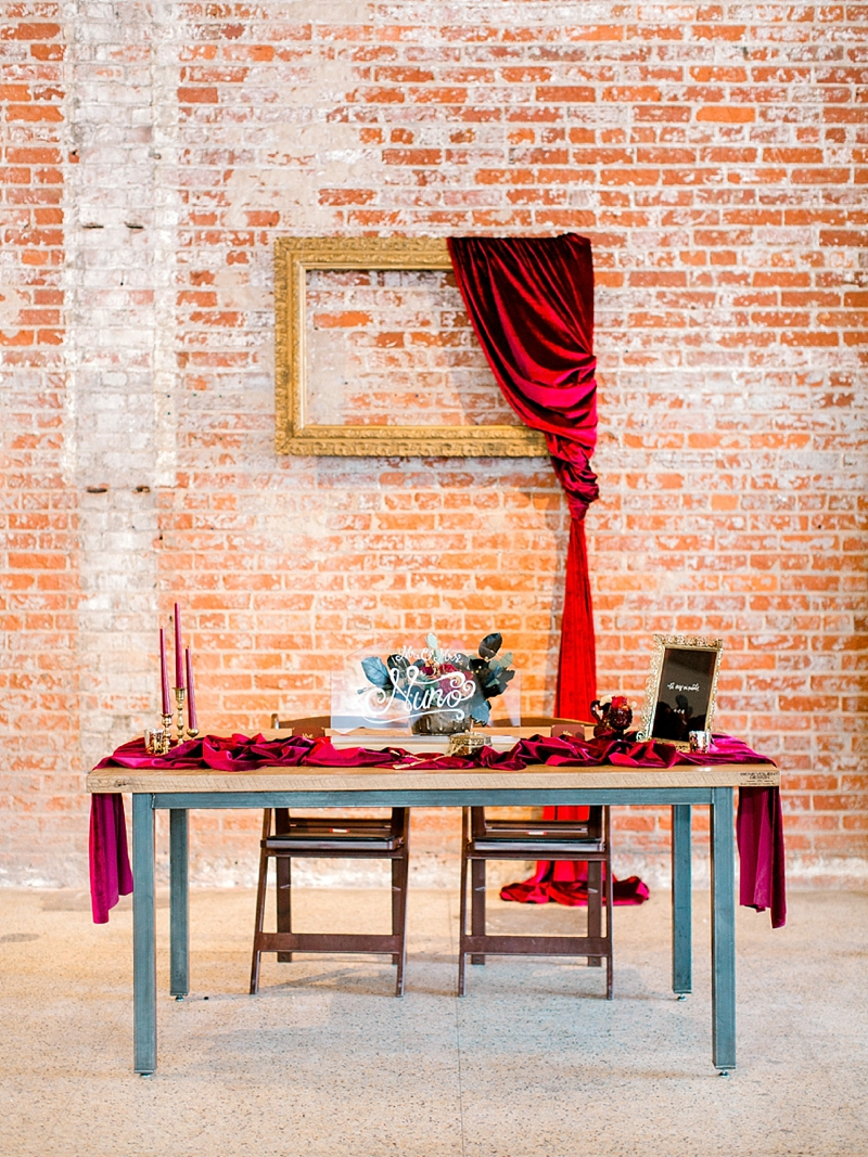 Elegant asymmetrical red velvet draping on gold frame for wedding backdrop