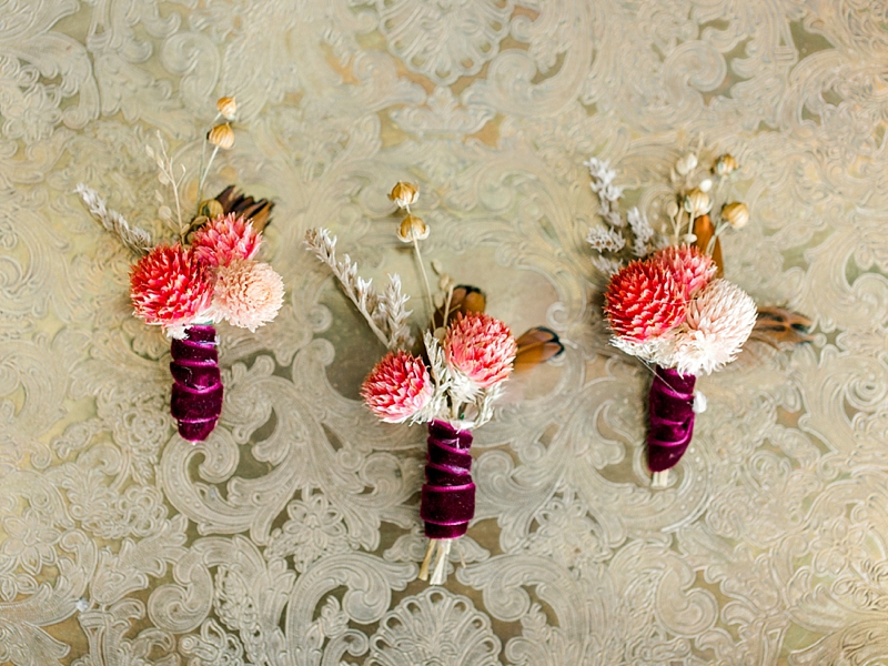 Dried botanical boutonnieres wrapped with wine colored velvet ribbon