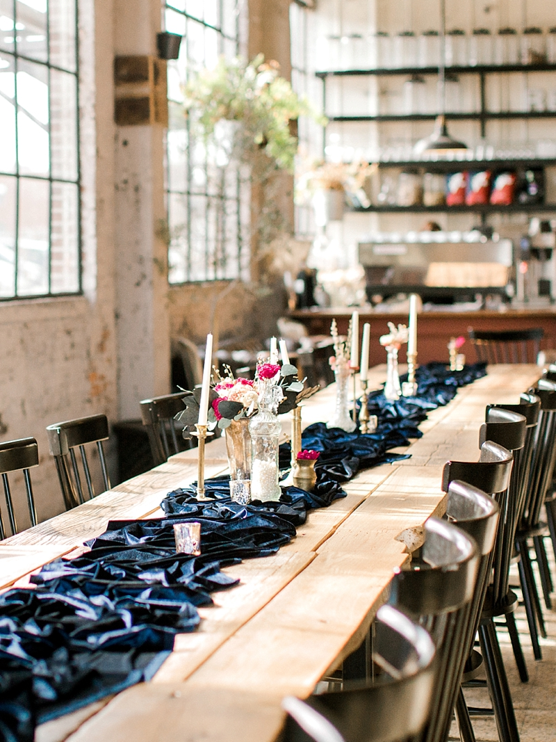 Long farm tables with blue velvet table runners for restaurant chic Virginia wedding