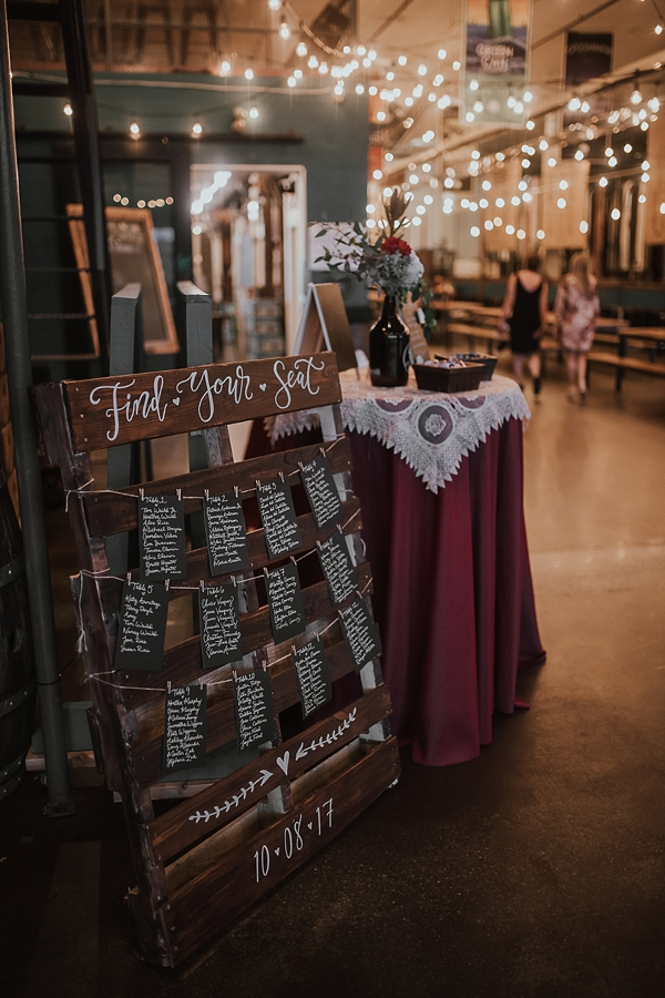Cute wooden escort card display with hand painted calligraphy and cards hanging by clothespins