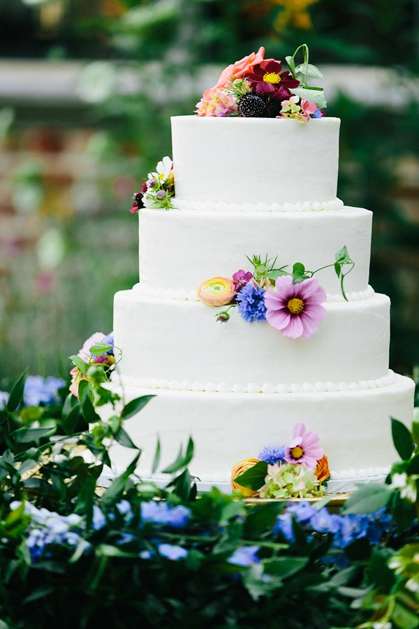 Simply elegant white tiered wedding cake with multi colored wildflowers