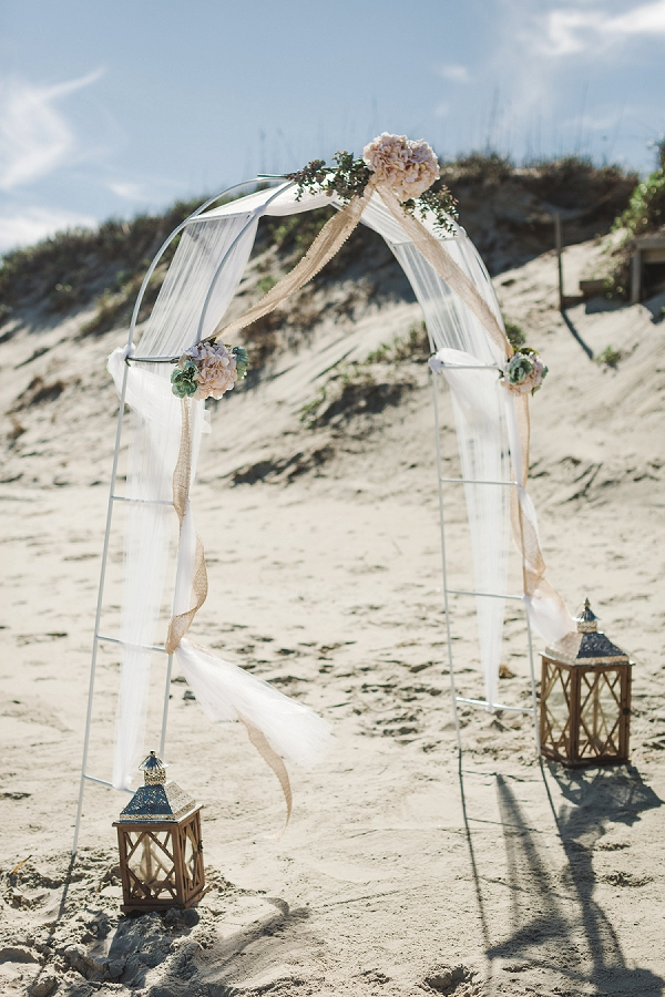 Simple beach wedding arch with white draping and large wooden lanterns