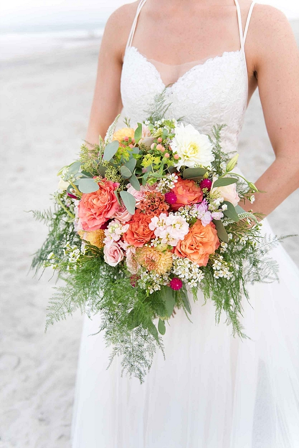 Cheerful and bright wedding bouquet with orange and pink flowers