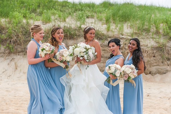 Bridesmaids in dusty blue dresses on the Outer Banks beach
