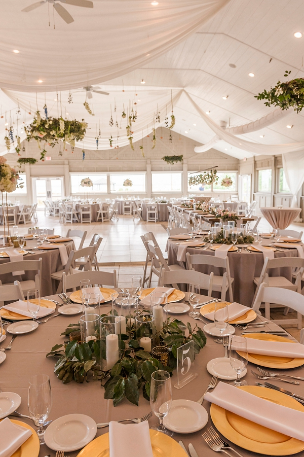 Gorgeous draped ceiling and florals hanging from the ceiling for romantic and whimsical wedding reception look
