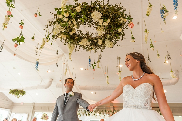 First dance of bride and groom and a glimpse at hanging florals from wedding ceiling