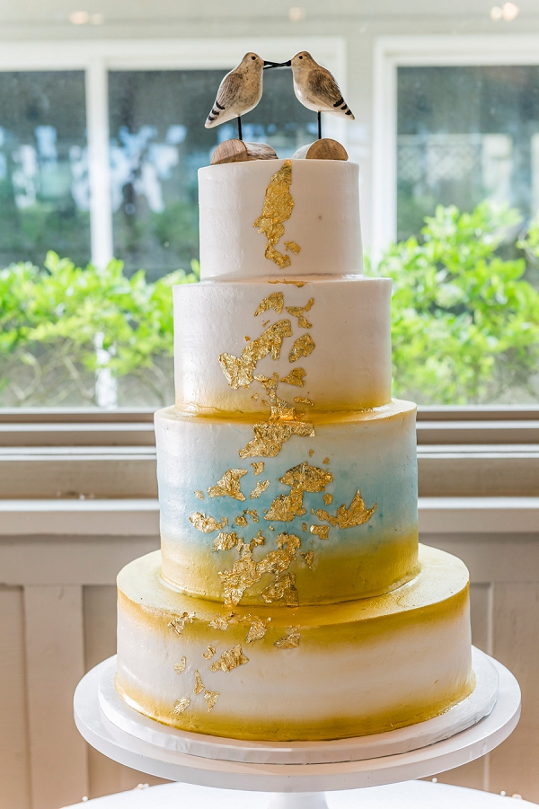 Turquoise and gold tiered wedding cake with adorable sandpiper cake topper for beach wedding