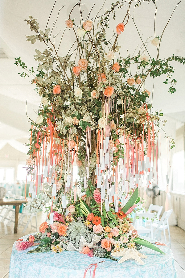 Beautiful turquoise and coral beach wedding hanging escort card tree with air plants and ginger