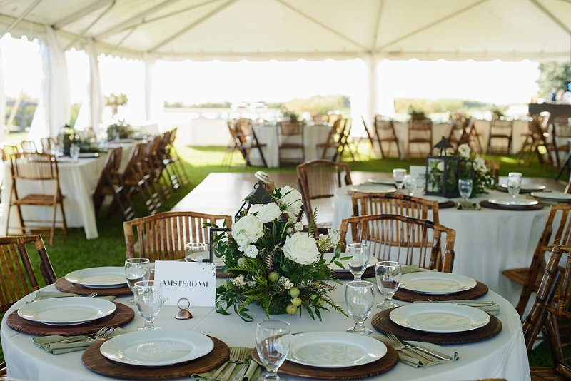 Beautiful Whalehead Club wedding reception with tropical wooden chairs and earthy wood chargers