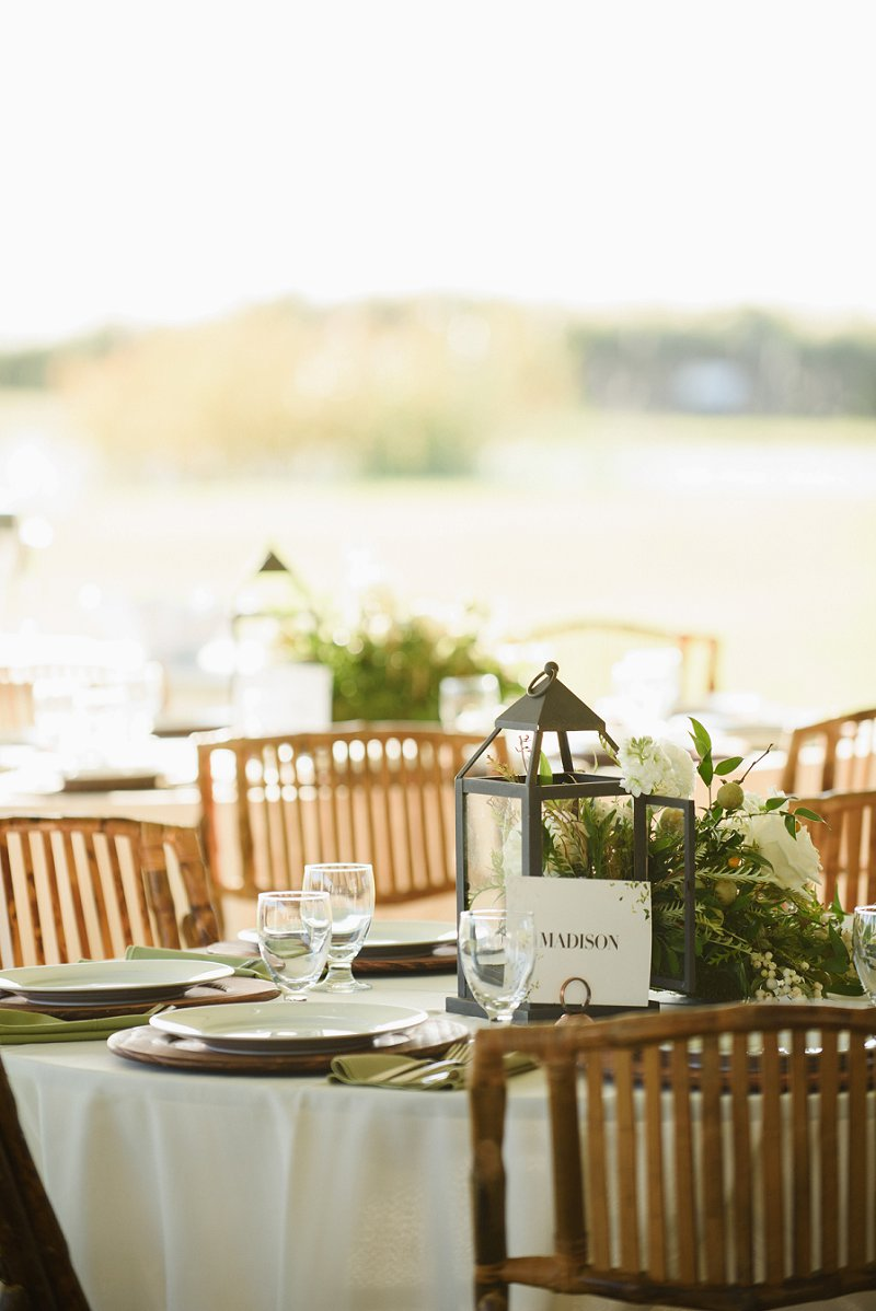 Greenery inspired wedding centerpieces with lanterns and town names for table numbers