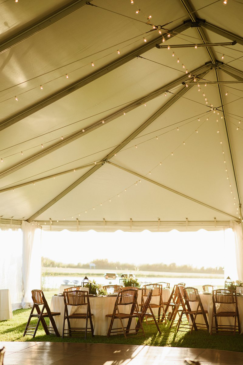 Tented country club beach wedding with bamboo folding chairs and waterside view