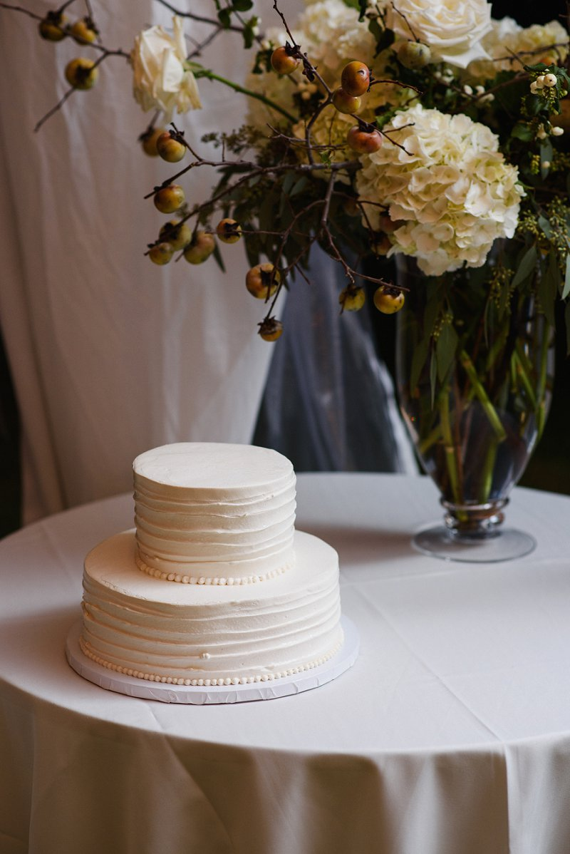 Simple and elegant two tier white wedding cake for beach wedding with a donut wall