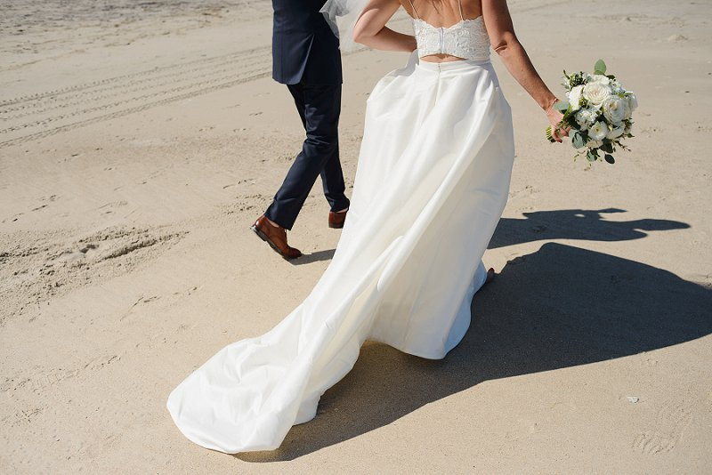 Peekaboo and flowy wedding dress detail for an elegant beach bride style