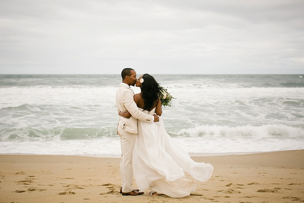 Windswept bride and groom portraits on the beach