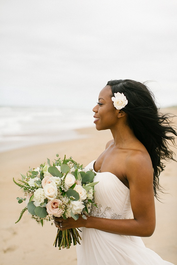 Windswept beach bride with flower in her hair