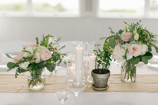 Short wedding centerpieces with roses and ferns on a linen table runner