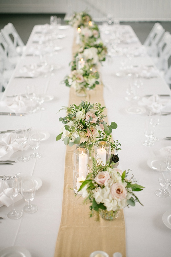 Low wedding reception floral centerpieces with ferns and dotted glass vases