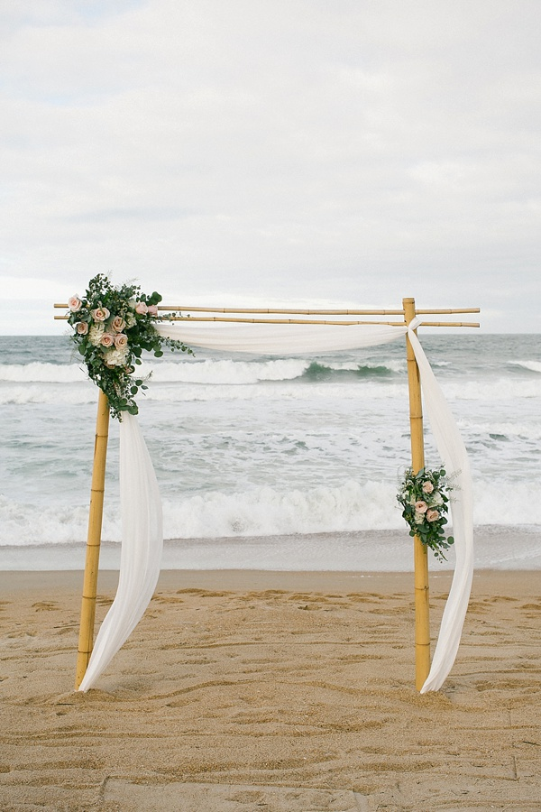 Bamboo wedding ceremony arch with white drapery and floral swag that includes roses and eucalyptus