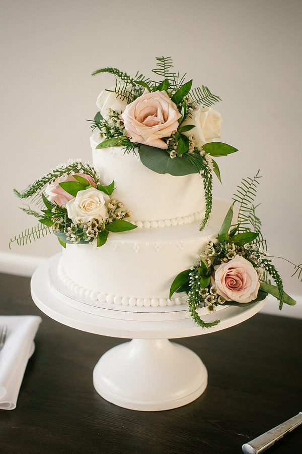 Small white wedding cake with dots and flowers on a cake stand