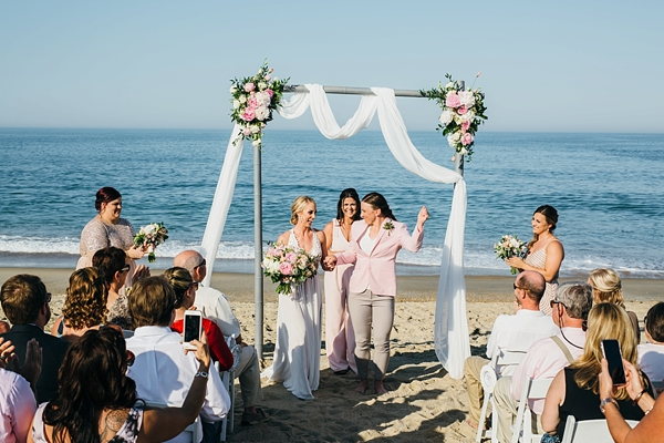 Beach wedding ceremony with simple and elegant wedding arch with floral swag and drapery