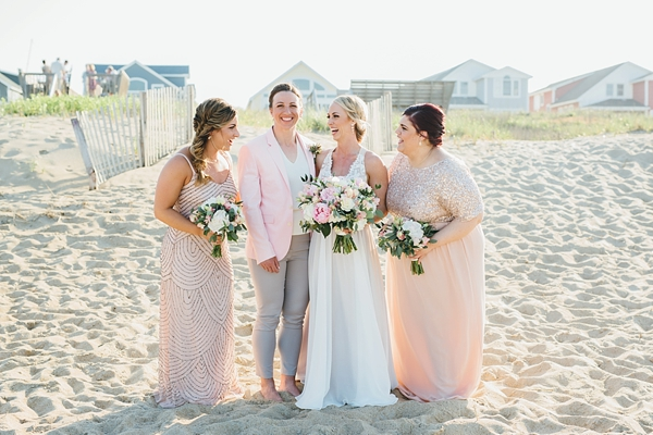 Pink and champagne colored bridesmaid dresses with bride in pink blazer jacket