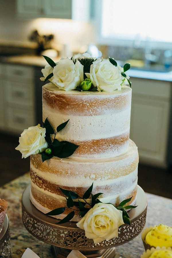 Semi naked wedding cake decorated with white roses