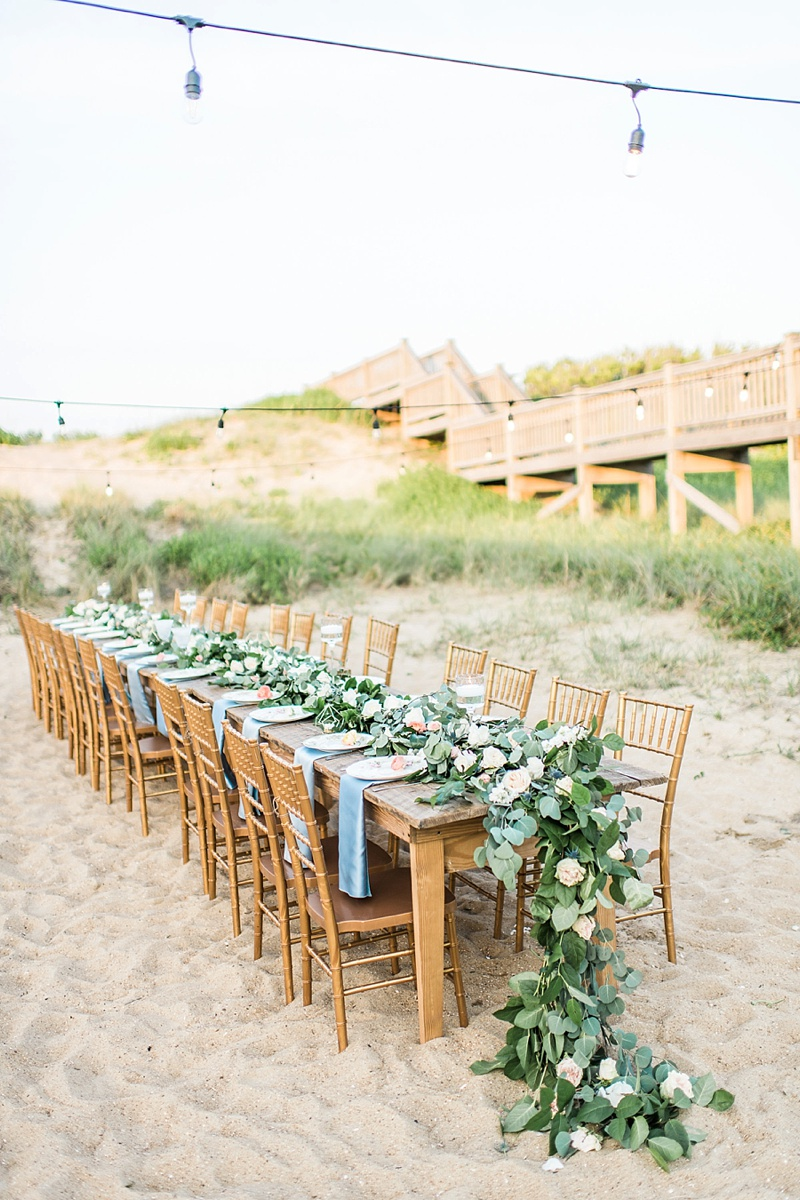 Outdoor wedding vow renewal beach reception with long wooden farm table with draping eucalyptus centerpiece garland