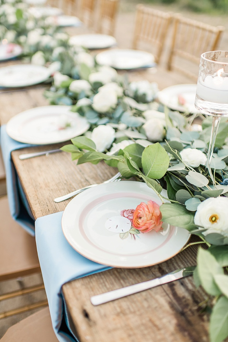 Long farm table with eucalyptus garland and vintage plates with sand dollars for beach wedding reception