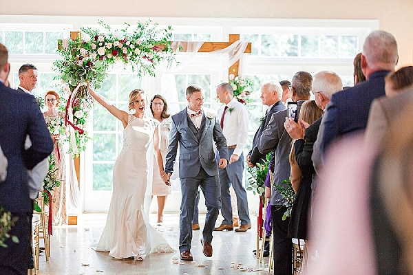 Gorgeous ceremony arch with asymmetrical flowers and tulle draping