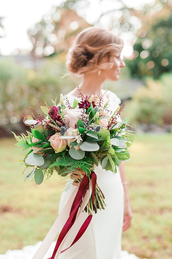 Fall bride with lush bouquet and burgundy red flowers and ribbon