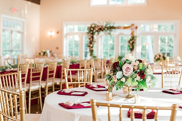 Burgundy maroon red linens and gold chiavari chairs for wedding reception setup