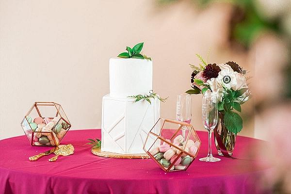 Simple white and geometric modern wedding cake with macarons