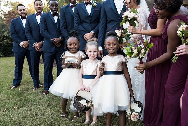 Adorable flower girls in gold sequins and navy blue sashes