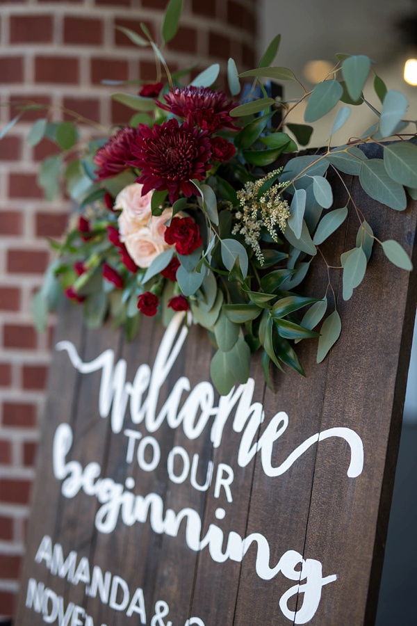 Hand lettered wooden sign with dark red dahlias and eucalyptus