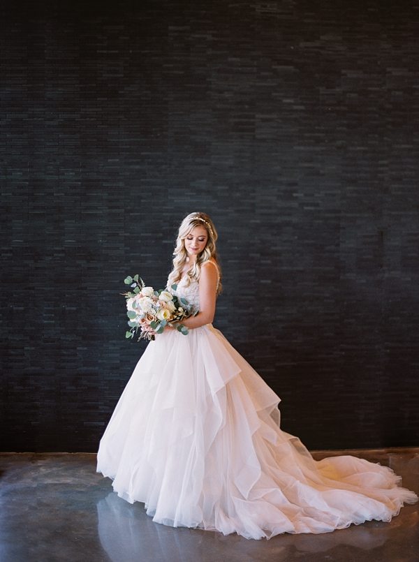 Blush pink wedding gown for an industrial bridal portrait in front of black subway tiles
