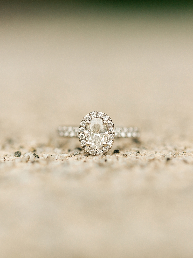 Classic oval solitaire engagement ring with border of diamonds around it and on the band