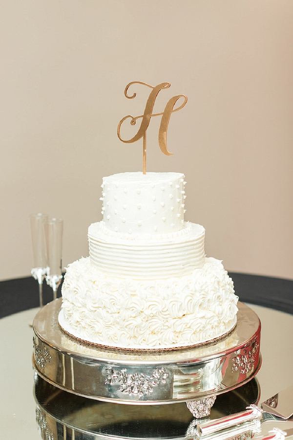 Simple white tiered Southern hummingbird wedding cake with gold monogram cake topper