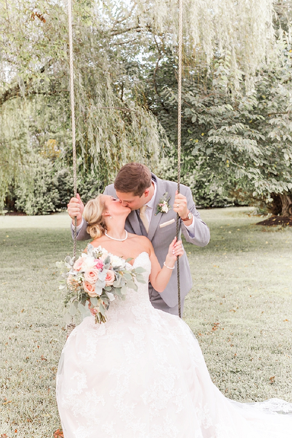 Bride and groom share a kiss on a rope swing