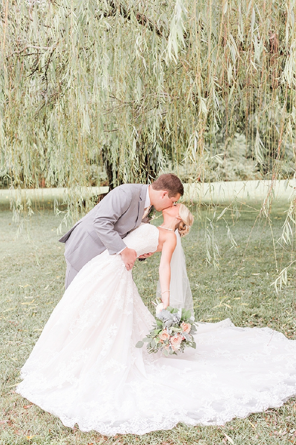 Sweet kiss under a weeping willow tree for rustic wedding