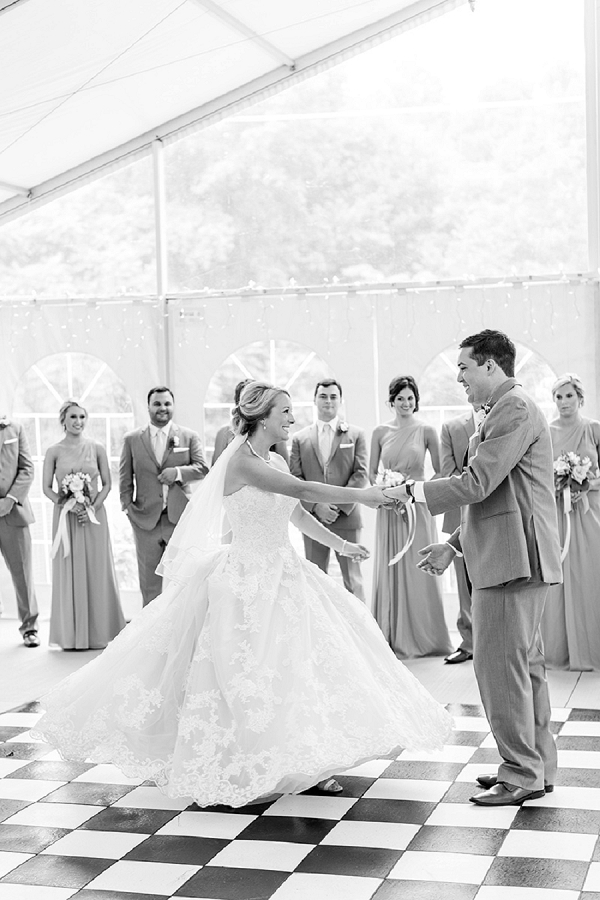 First dance moment on black and white dance floor in a wedding reception tent