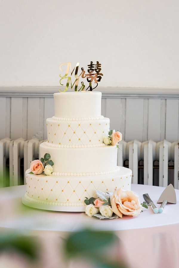 White quilted wedding cake with gold Chinese cake topper that says Double Happiness