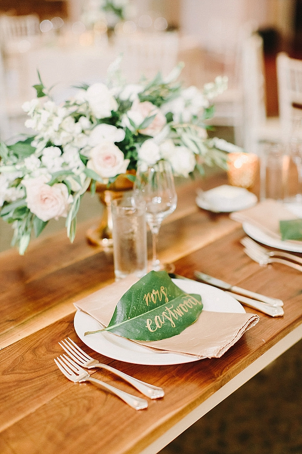 Green leaves with gold calligraphy as wedding place cards