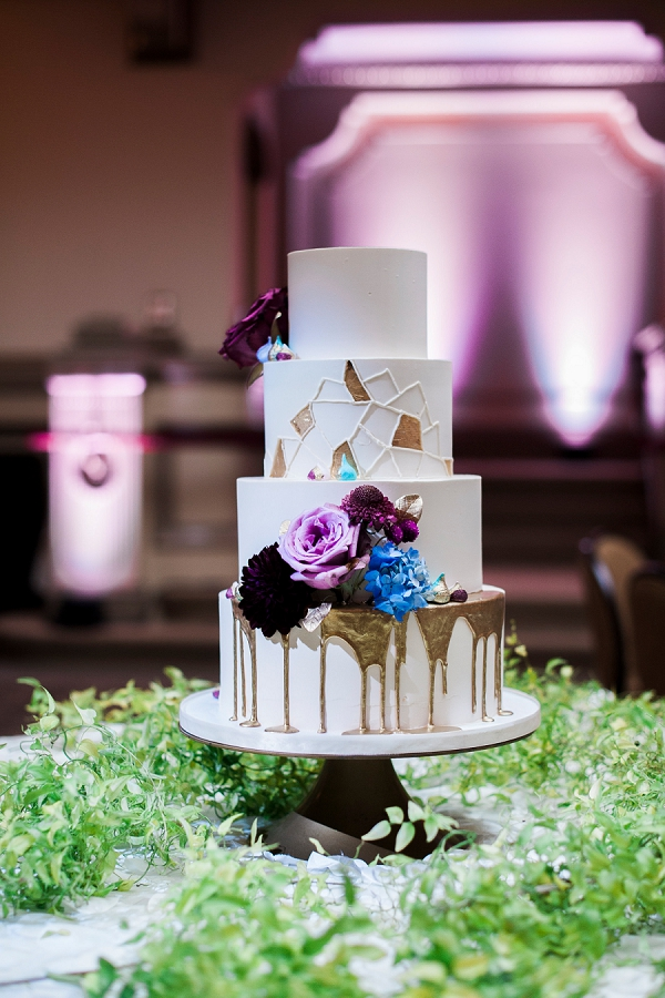 Geometric modern wedding cake with gold dripping surrounded by greenery