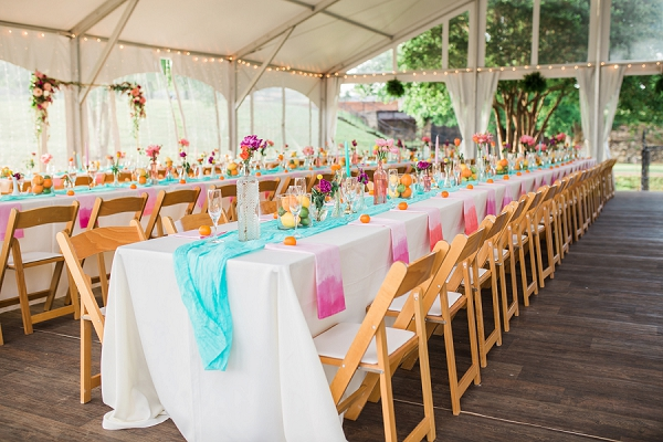 Tented wedding reception with long tables and dip dye napkins