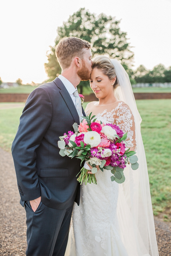 Bright pink and white wedding bouquet held by bride in long sleeved lace wedding dress