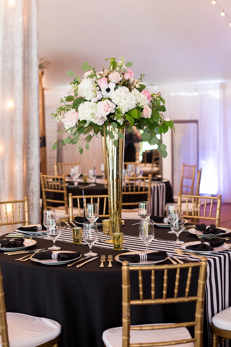 Tall gold centerpiece with pink and white flowers for classic black tie wedding