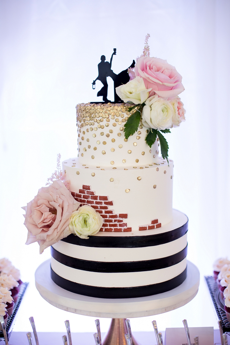 Fun black and white striped wedding cake with brick and gold confetti details