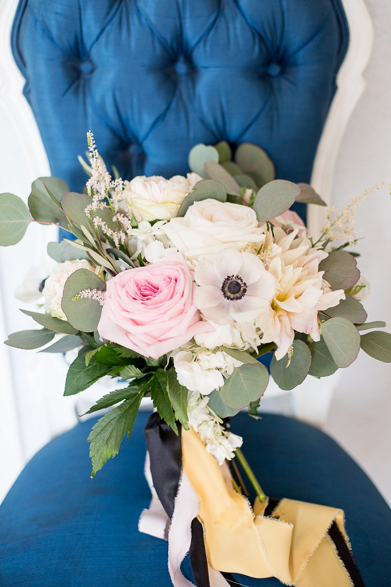 White and pink wedding bouquet with gold and black ribbons
