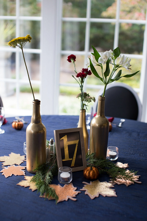 Handmade fall wedding centerpiece with autumn leaves and wine bottles