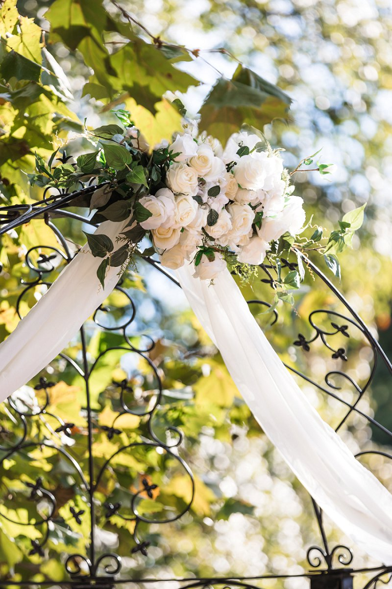 Classic wedding ceremony arch floral swag with white roses and drapery